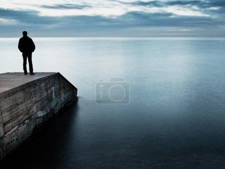 Photo pour L'homme est debout sur une jetée regardant le coucher du soleil - image libre de droit