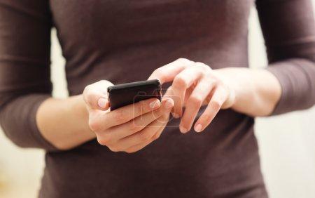 Photo pour Gros plan d'une femme à l'aide de la puce de téléphone mobile - image libre de droit