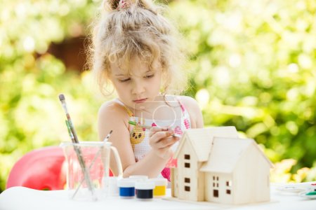 Portrait of little girl paints wooden model of house,  summer ou