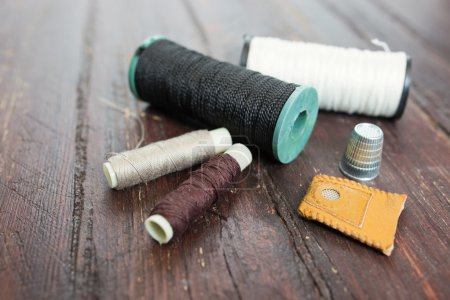 Thimble and needles for sewing close-up on a wood background. ma
