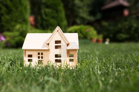 Wooden model of house on grass,  summer outdoor, new home concep