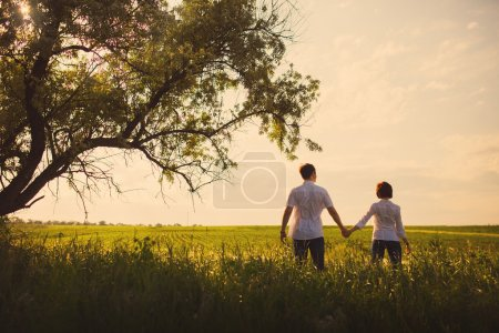 Happy couple standing in the field at the sunset, tinted photo