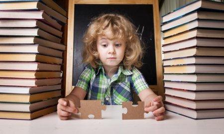 Photo pour Portrait d'écolière mignonne pensant tout en étant assis avec pile de livres à table, concept d'éducation - image libre de droit