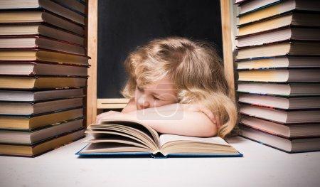 Photo pour Jeune fille endormie sur le livre au bureau - image libre de droit