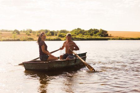 Happy romantic couple rowing a boat on lake.