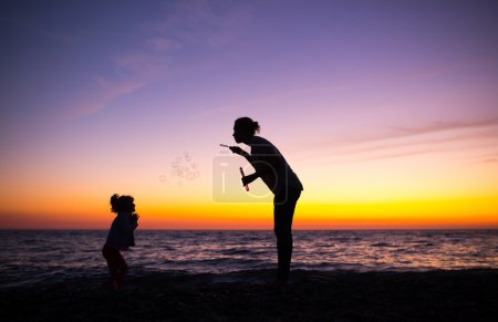 Silhouette of Mother and daughter playing with soap bubbles on t