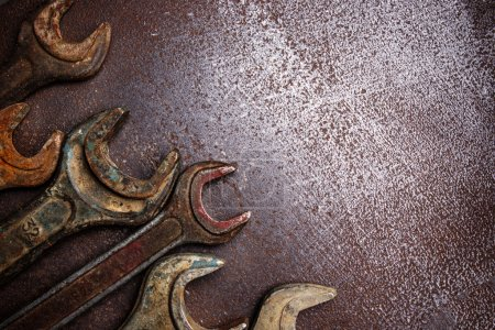 Old rusty wrenches on a metal table