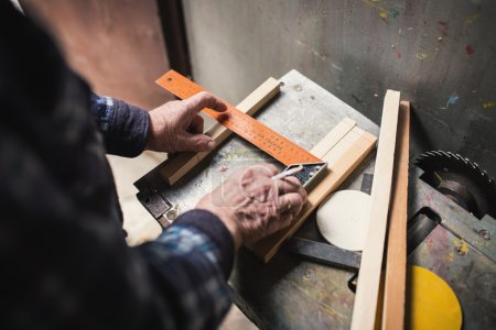 Photo for Old carpenter taking measurement of a wooden plank - Royalty Free Image