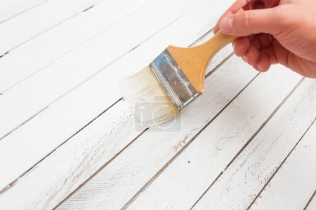 Hand holding brush and paint wooden surface in white