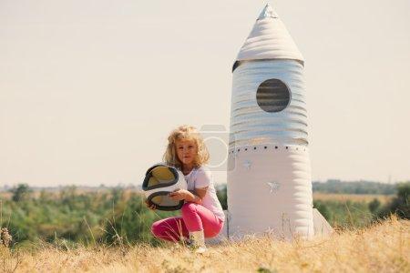 Photo pour Joyeux enfant habillé d'un costume d'astronaute jouant avec une fusée fabriquée à la main. En plein air. Rétro teinté - image libre de droit