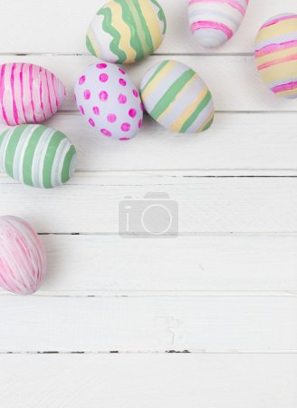 Photo for Easter eggs painted in pastel colors on a white wood background - Royalty Free Image