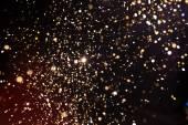 Photo of golden glitter on a black background. Golden explosion