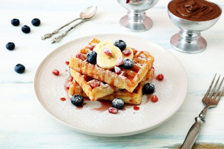 Photo for Waffles with fresh fruits on kitchen table background - Royalty Free Image