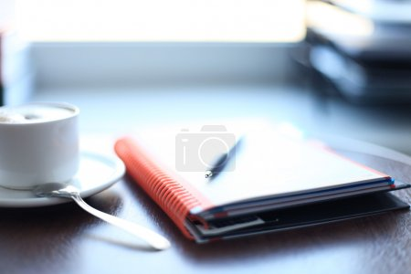 Office supplies and coffee cup on table