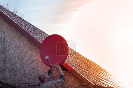 Photo for Man installs a satellite TV dish on the roof of the house. Independent TV communication in a private home. - Royalty Free Image