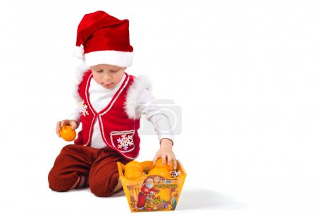 Photo for Gnome adds tangerines in the box for candy - Royalty Free Image