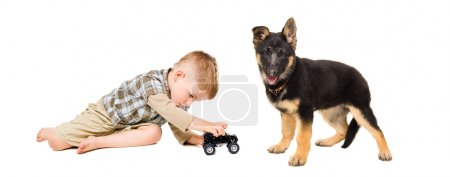 Boy playing a toy car with a puppy