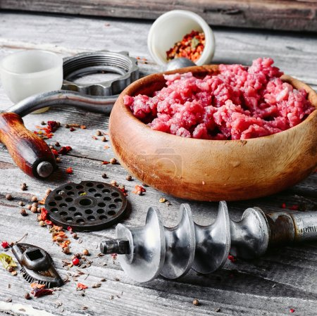 Photo for Wooden dish, with meat and parts of the disassembled grinder - Royalty Free Image