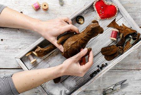 Photo pour Mains de femmes dans le processus de fabrication de jouets en ours doux et d'outils à coudre - image libre de droit