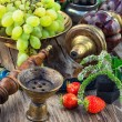 Old smoking  hookah and bunch of grapes on wooden ...