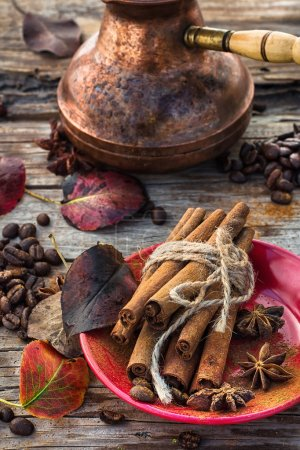 Photo for Stylish porcelain Cup of coffee on  background decorated with spices and strewn with autumn leaves - Royalty Free Image