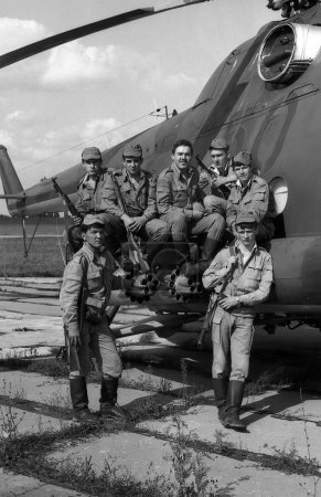 A squad of soldiers standing near a combat helicopter Mi-8. Film scan. Large grain