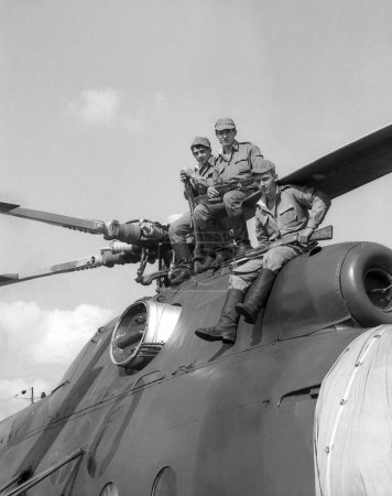 Soldiers sitting on a combat helicopter Mi-8. Film scan. Large grain