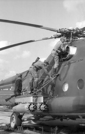 Soldiers inspect a combat helicopter Mi-8. Film scan. Large grain