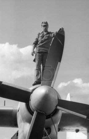 A soldier stands on the wing, near the turboprop of the military transport aircraft AN-24. Film scan. Large grain