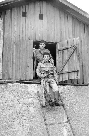 Two soldiers posing with guns in the attic of an old house. Film scan. Large grain