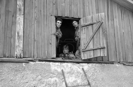 Three soldiers with weapons in the attic of an old house. Film scan. Large grain