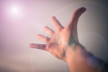 Photo pour Main d'un homme qui tend vers le ciel. Image tonique de couleur . - image libre de droit