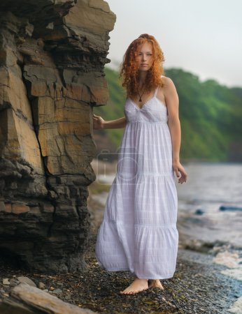 Photo for Beautiful redhead woman goes along the coast. - Royalty Free Image