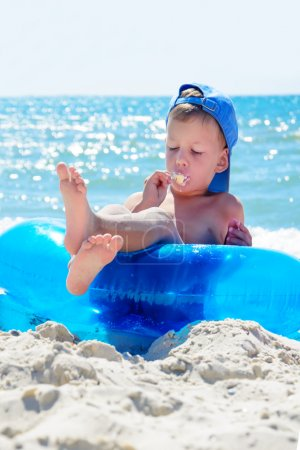 kid with ice cream on beach sitting in water tube