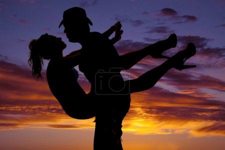 silhouette of a woman held by man in the sunset