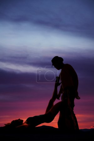 silhouette of a woman laying on back leg up on cowboy