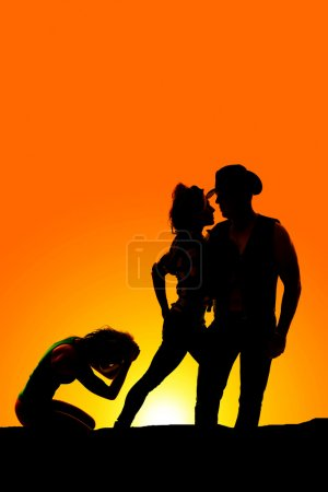 silhouette of woman kneeling hands on head in the sunset near a