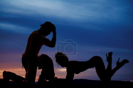 silhouette of woman on elbows and knees feet up cowboy kneel