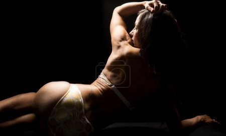 Photo for A woman in her golden bikini in the shadows, with tattoo on her back. - Royalty Free Image