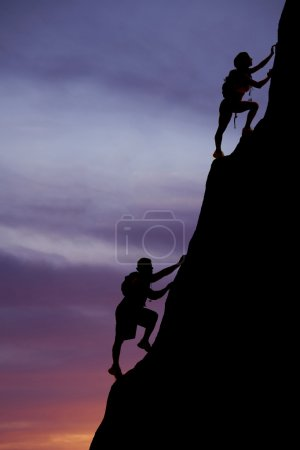 Silhouette man and woman backpackers climb up
