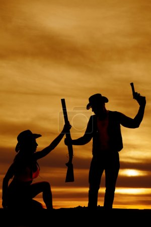 silhouette of cowgirl and cowboy grab gun