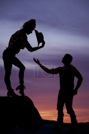 silhouette of man hand reaching up to a woman