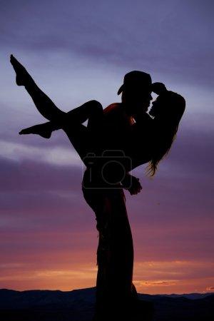 cowboy holding woman kiss
