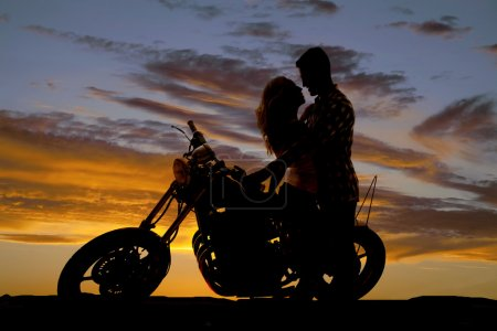 silhouette couple kiss on motorcycle