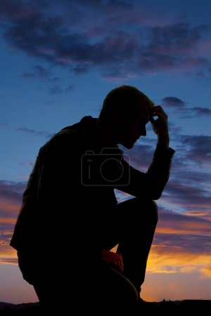 silhouette of man kneel in sunset hand on head