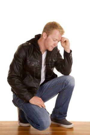 Man on one knee in back jacket looking down