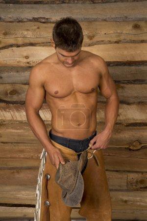 Photo pour Un cow-boy regardant vers le bas avec sa chemise au large, s'accrochant à son chapeau. - image libre de droit