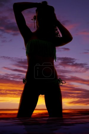 Photo for A silhouette of a woman kneeling down with her hands in her hair. - Royalty Free Image