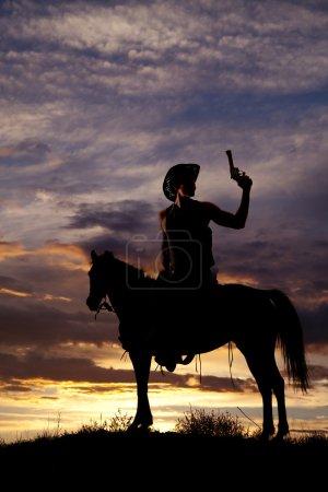 Cowboy with gun on horse