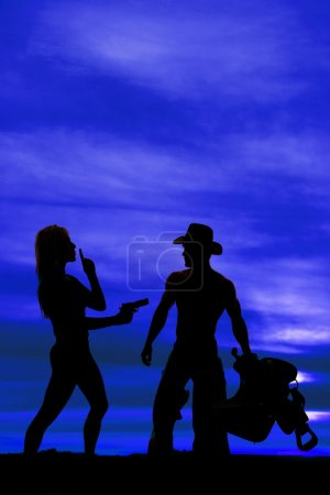 Photo pour A silhouette of a woman pointing her gun, with her finger up to her mouth, next to her cowboy. - image libre de droit